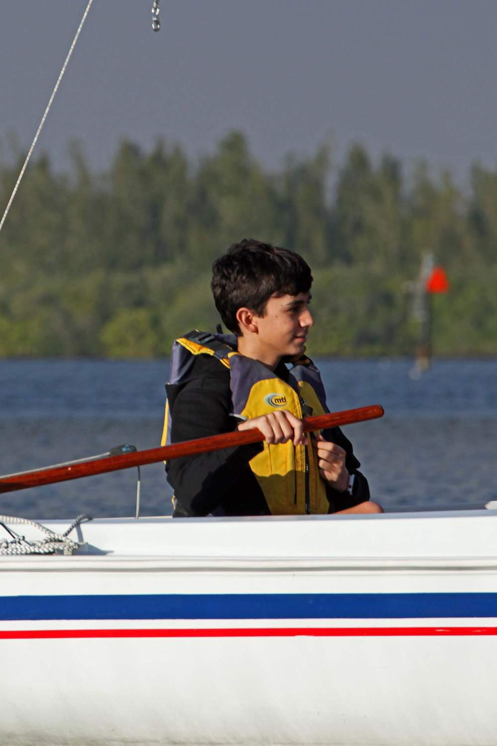 One young man looking to the side, sailing