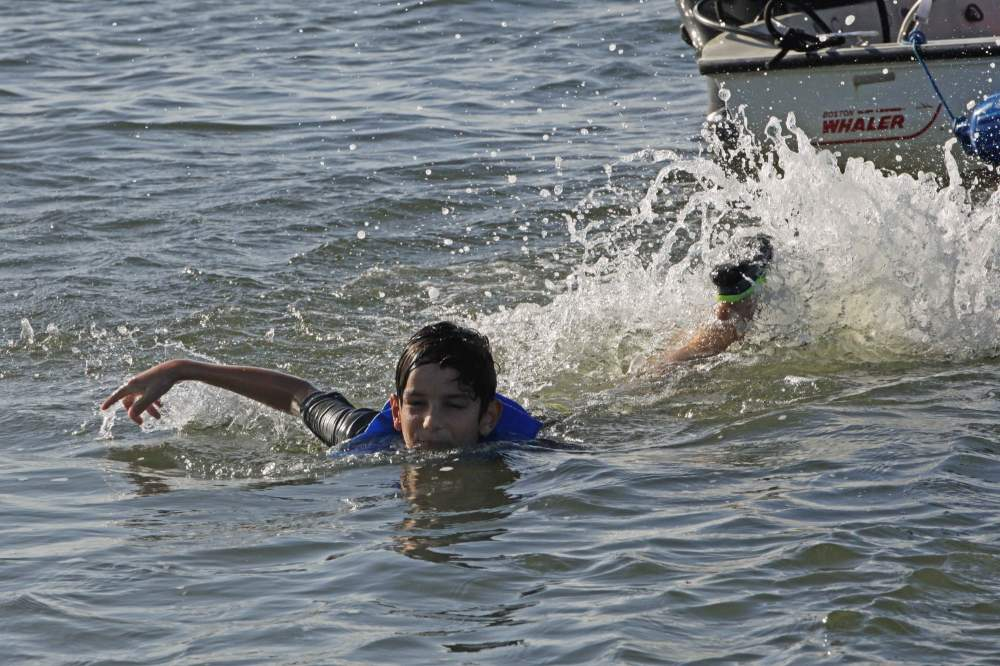 Young boy swimming away from boat